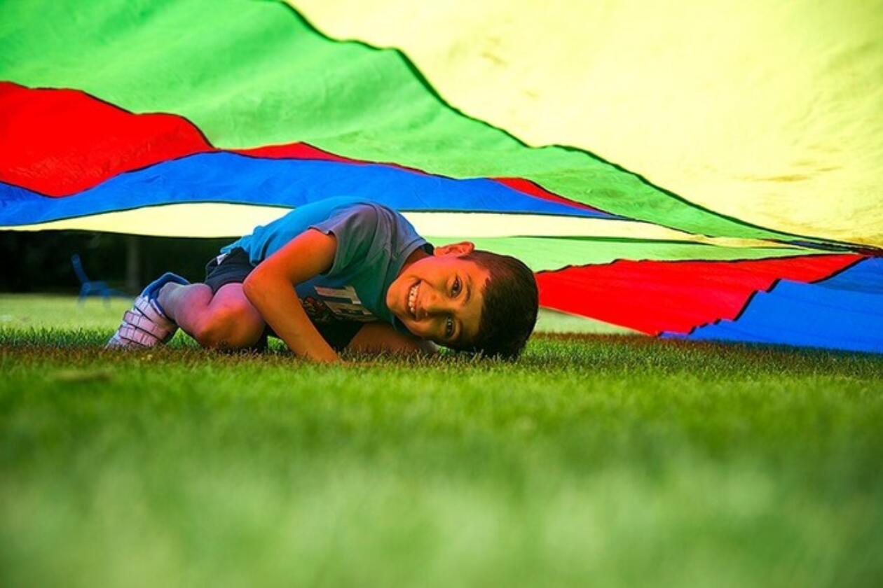 Kind unter Spiel-Fallschirm